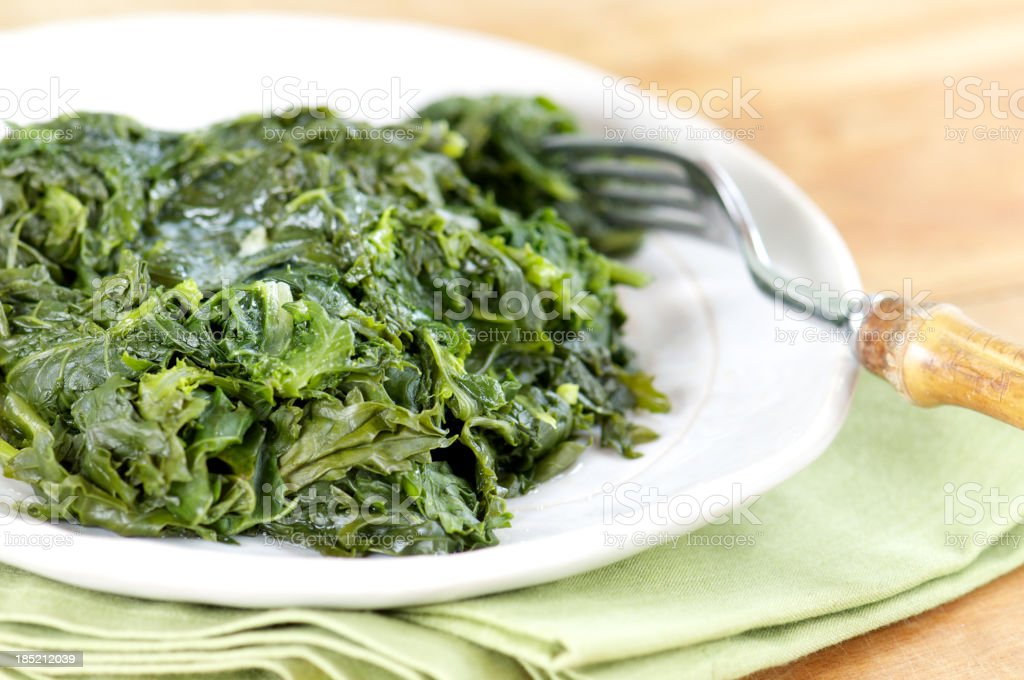 A plate of Southern style braised greens next to a fork stock photo
