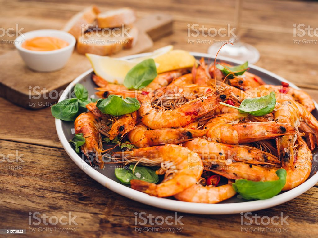 Plate of spicy barbecued prawn on a wooden table stock photo