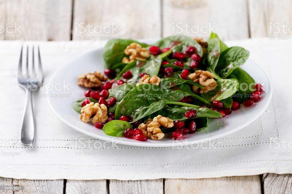 Plate of spinach salad with pomegranate and walnuts stock photo