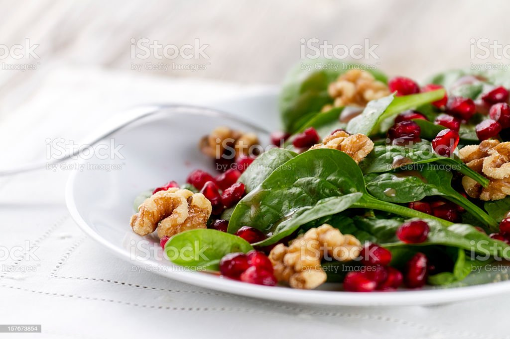 Plate of spinach salad with pomegranate seeds and walnuts stock photo
