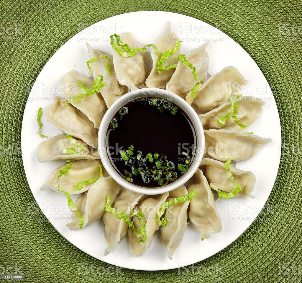Plate of steamed dumplings & brown soy sauce stock photo