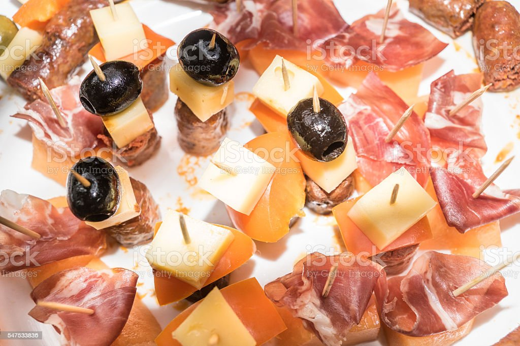 Plate of tapas with melon, ham and olives stock photo