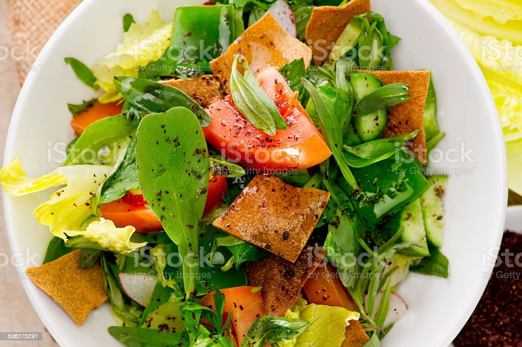 Plate of traditional Arabic salad fattouch on a wooden plate stock photo