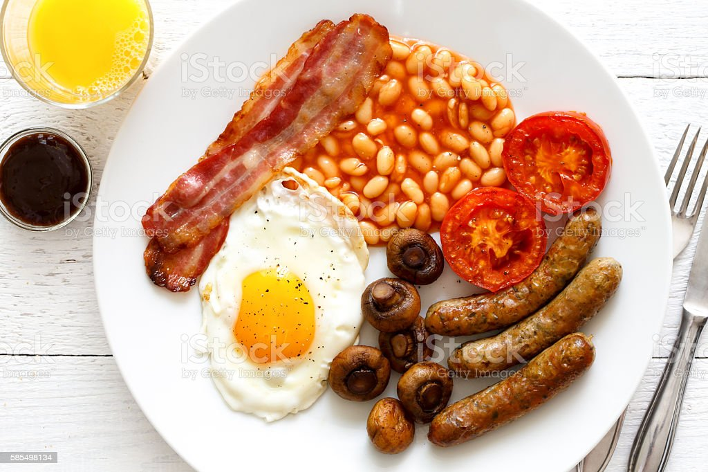 Plate of traditional fried English breakfast with orange juice f stock photo