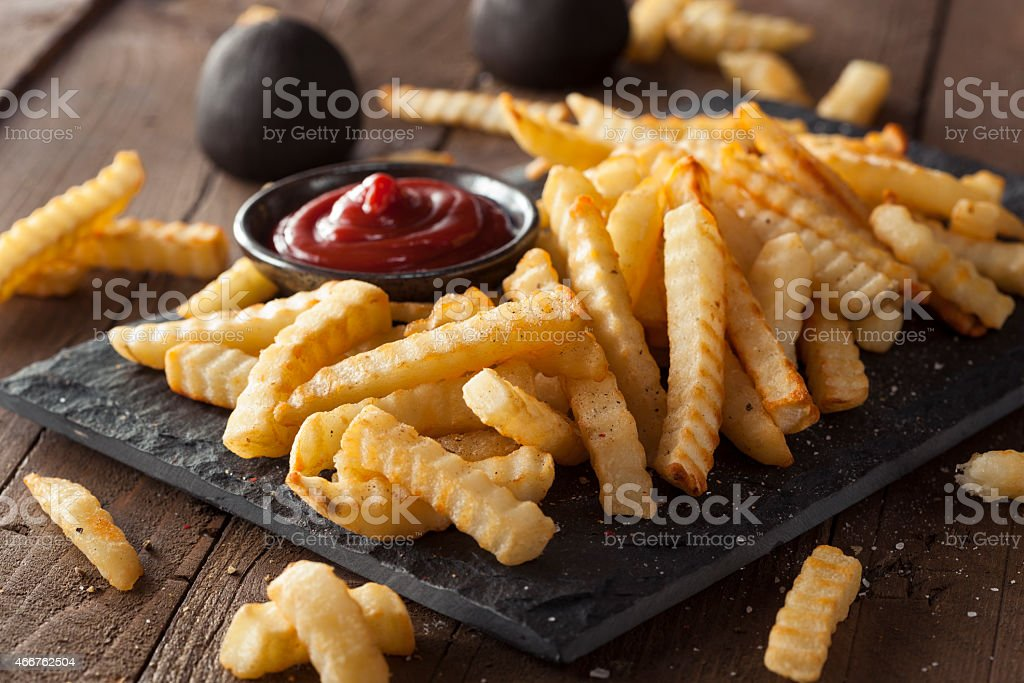 A plate of unhealthy baked crinkle French fries and ketchup stock photo
