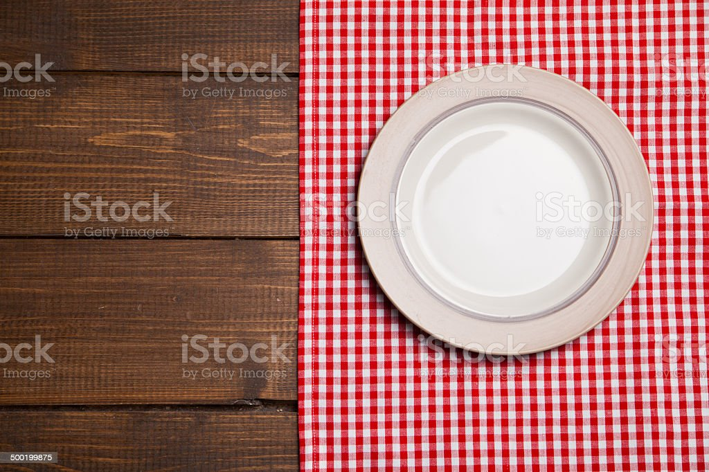 Plate on wooden table with red checked tablecloth stock photo