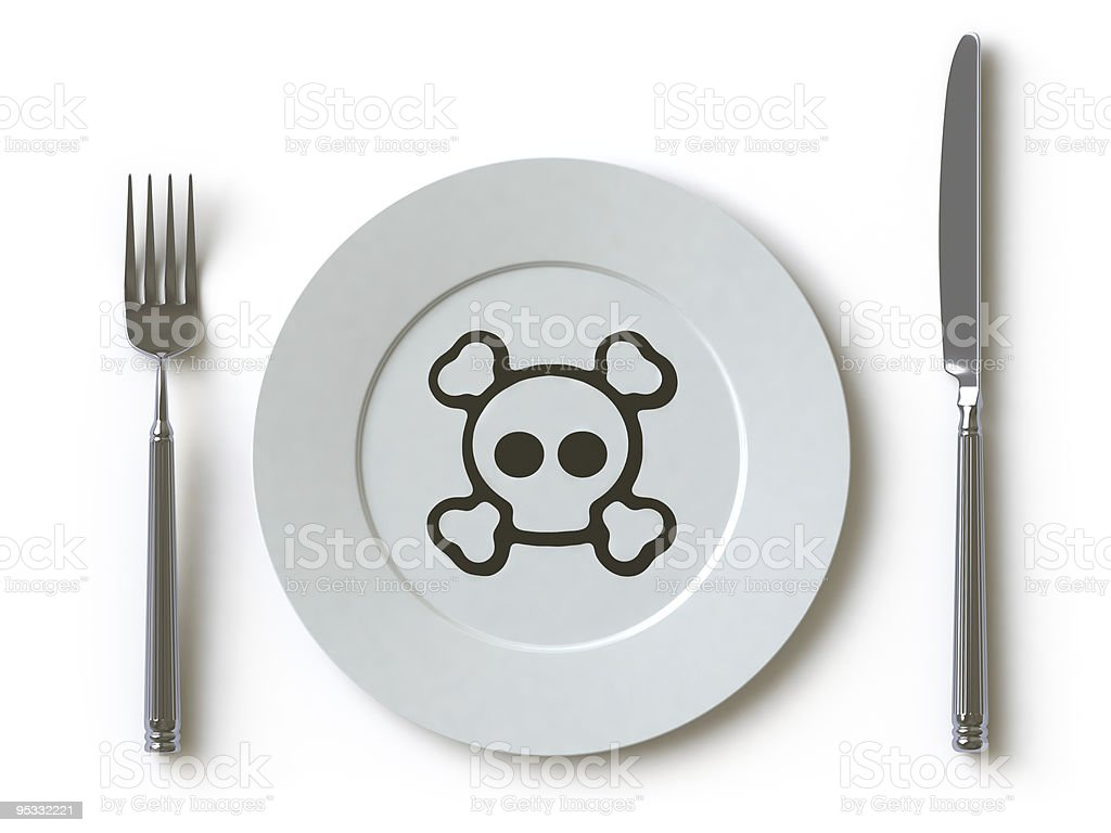 Plate with a skull and crossbones laying next to silverware royalty-free stock photo