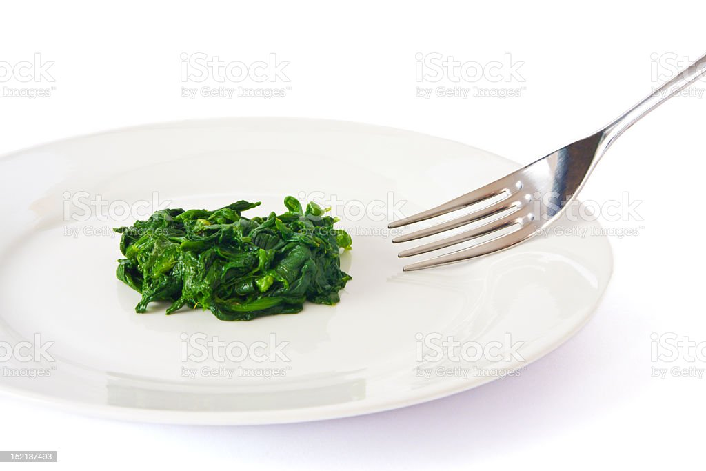 A plate with a small amount of spinach on it next to a fork  royalty-free stock photo