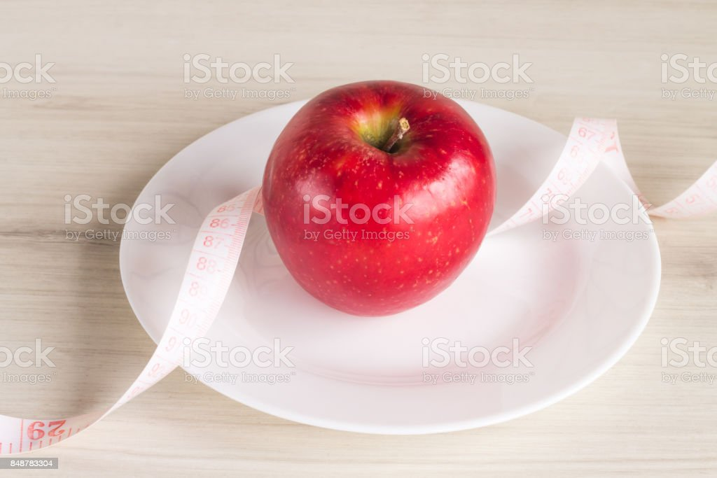 Plate with apple and measuring tape stock photo