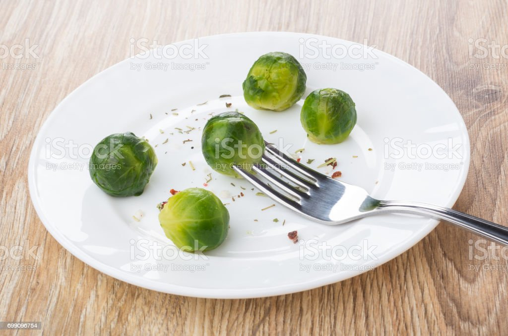 Plate with brussels sprouts, strung cabbage on fork stock photo