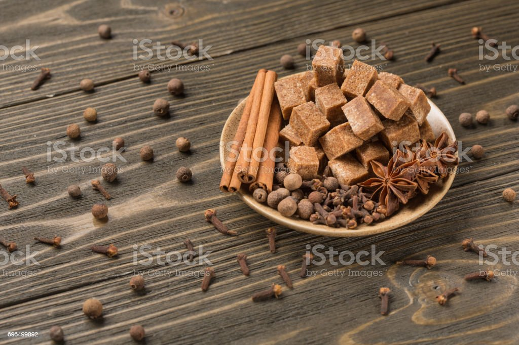 Plate with dark sugar and spices on the boards stock photo