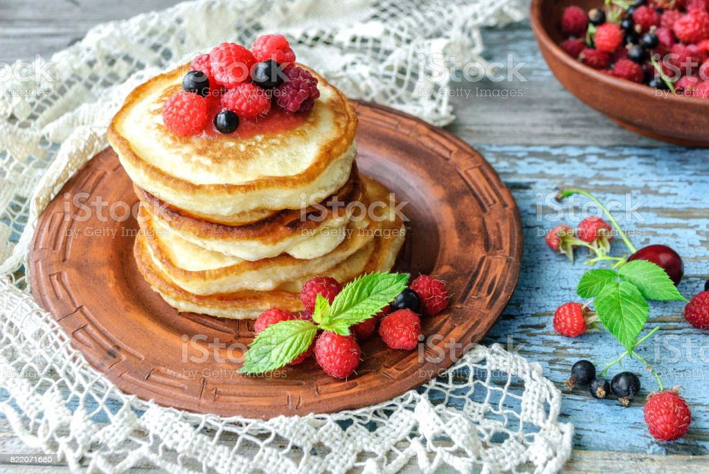 Plate with delicious pancakes and berries on table stock photo