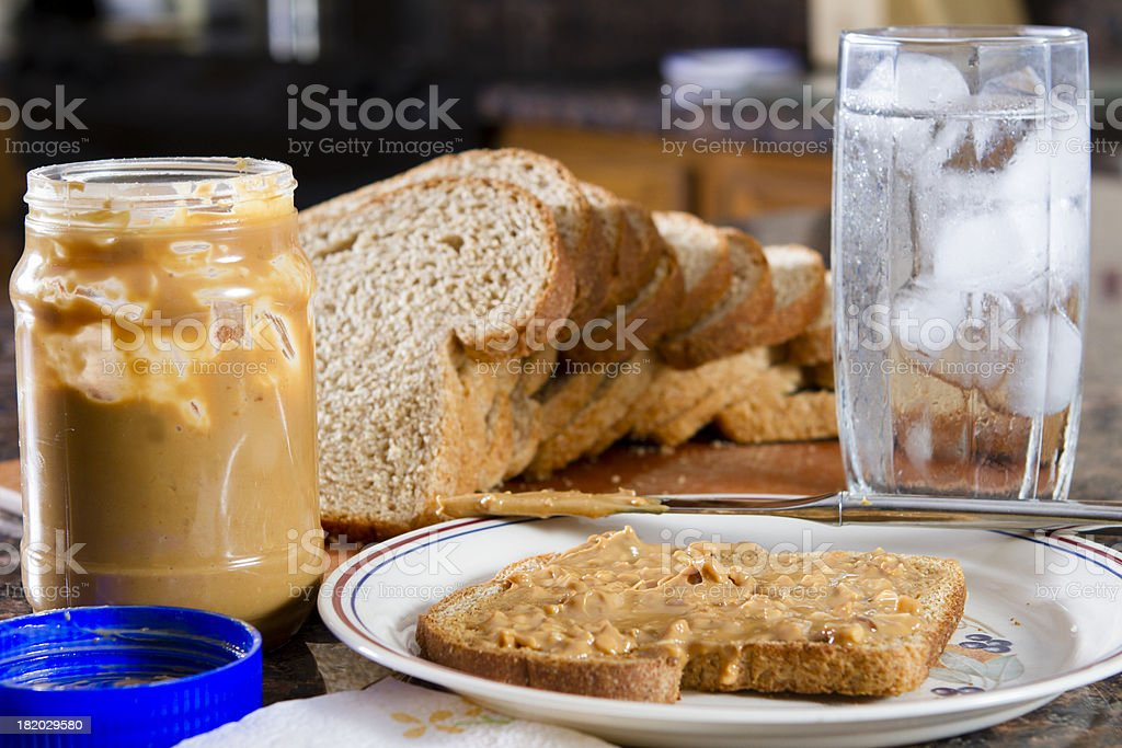 Plate with peanut butter on wheat bread on the counter. stock photo