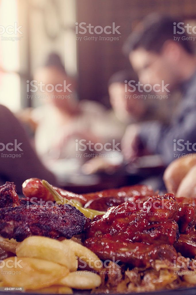 Plate with roasted meat, sausages and potatoes stock photo