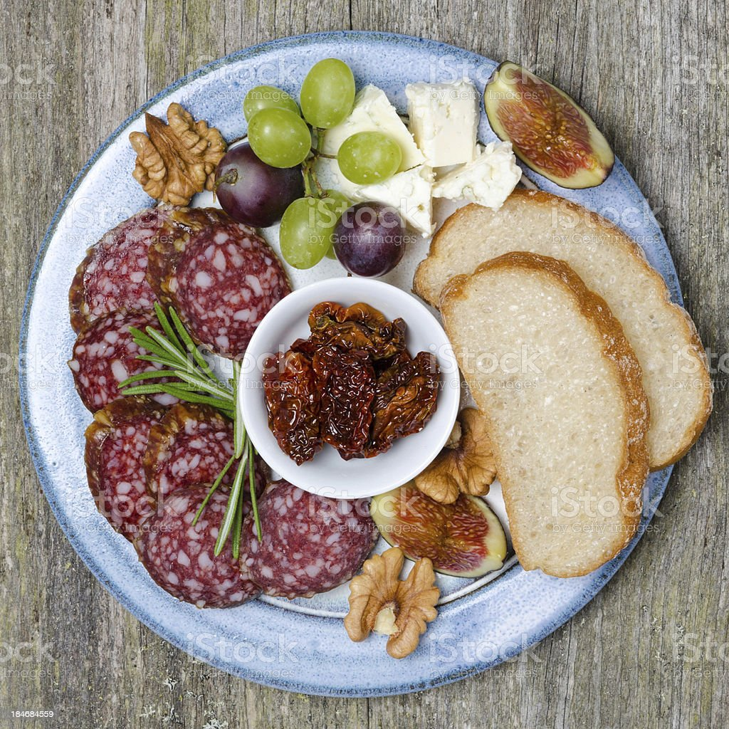 Plate with snacks, sausage, cheese, nuts and fruit royalty-free stock photo
