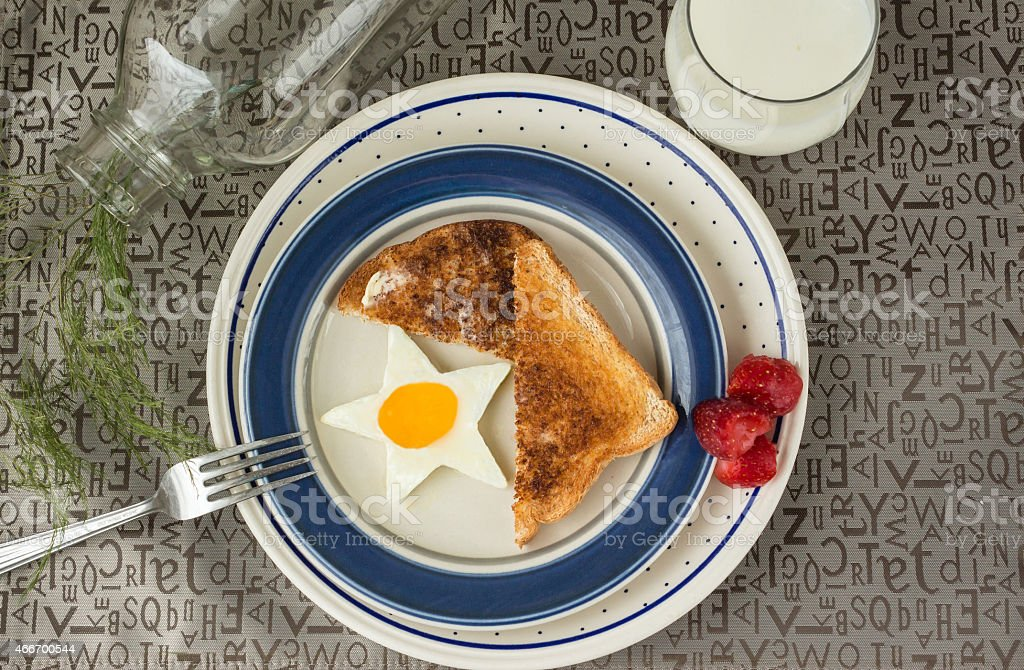 plate with star shaped fried egg and toast with milk stock photo