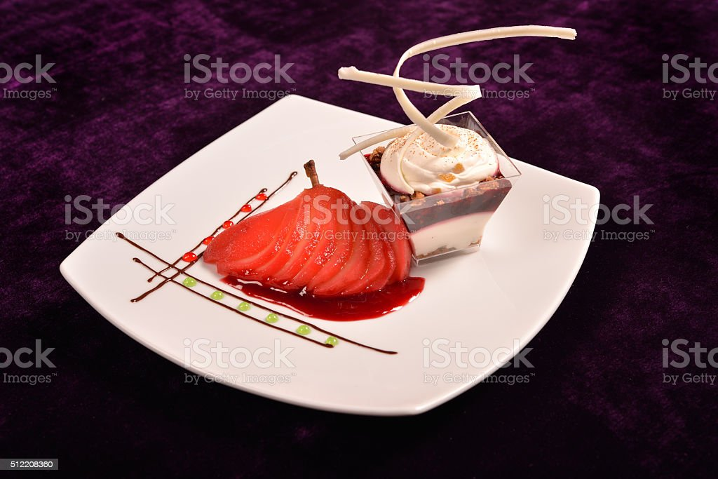 Plated dessert with poached pears in white porcelain plate stock photo