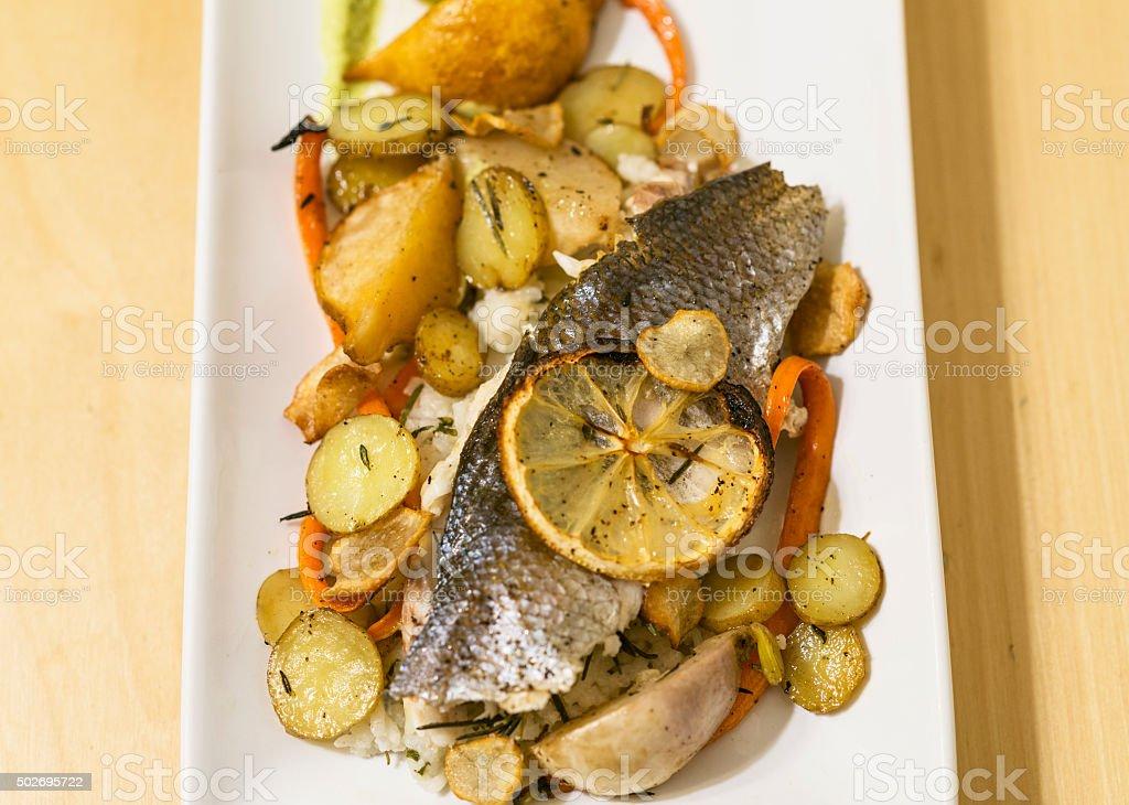 Plated Mediterranean Seabass with Lemon and Veggies - Branzino stock photo