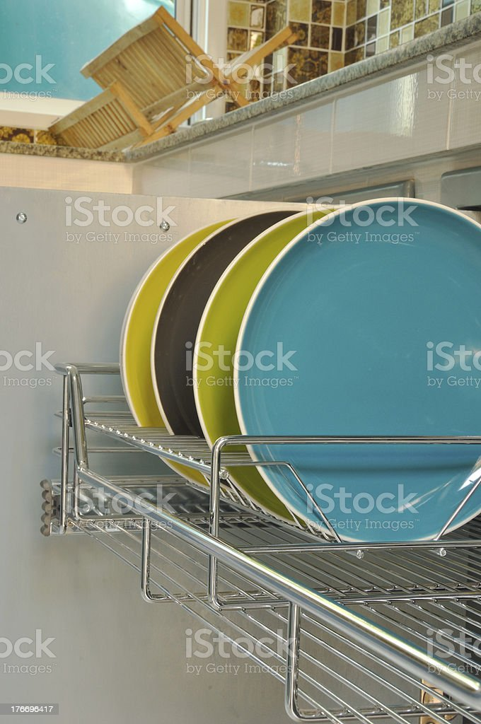 plates in stainless rack within cabinet stock photo