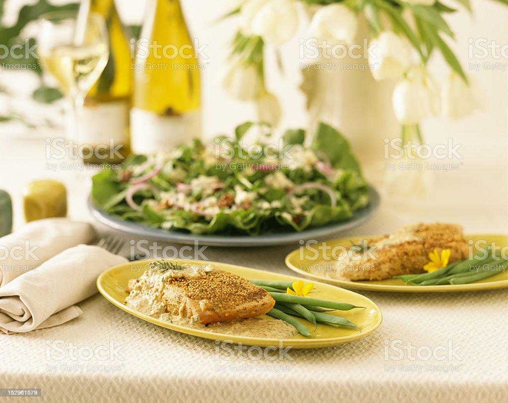 Plates of Salmon with Mustard sauce, salad, and white wine. royalty-free stock photo