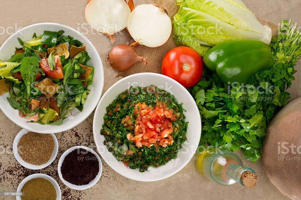 Plates of traditional Arabic salad fattouch and tabbouleh stock photo