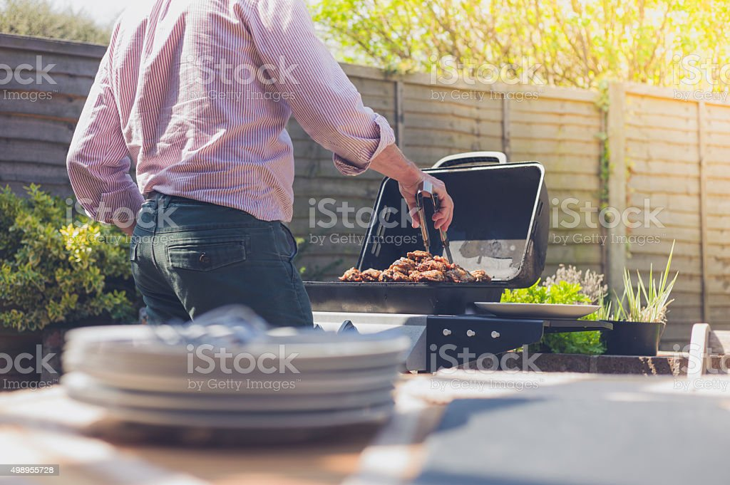 Plates on a table outside with man in background stock photo