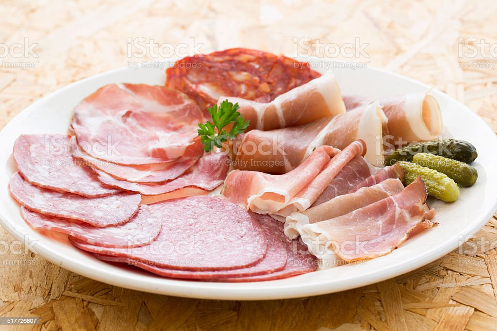 Platter of different ham Meat, salami and gherkin stock photo