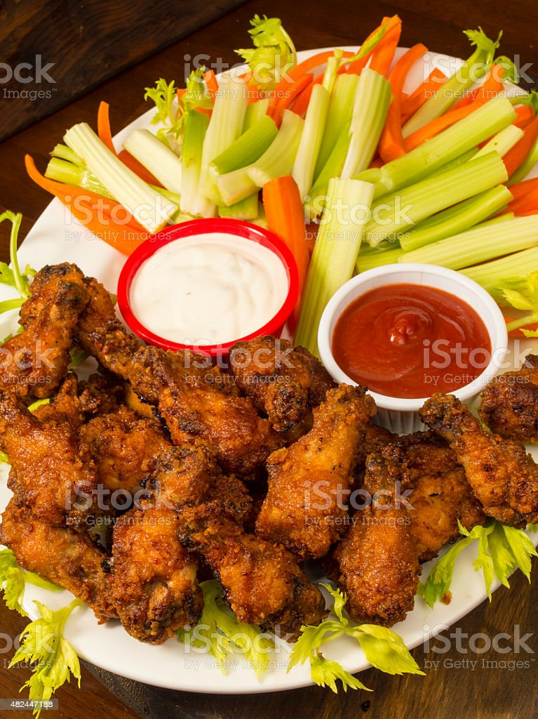 platter of hot and spicy chicken wings with veggie sticks stock photo