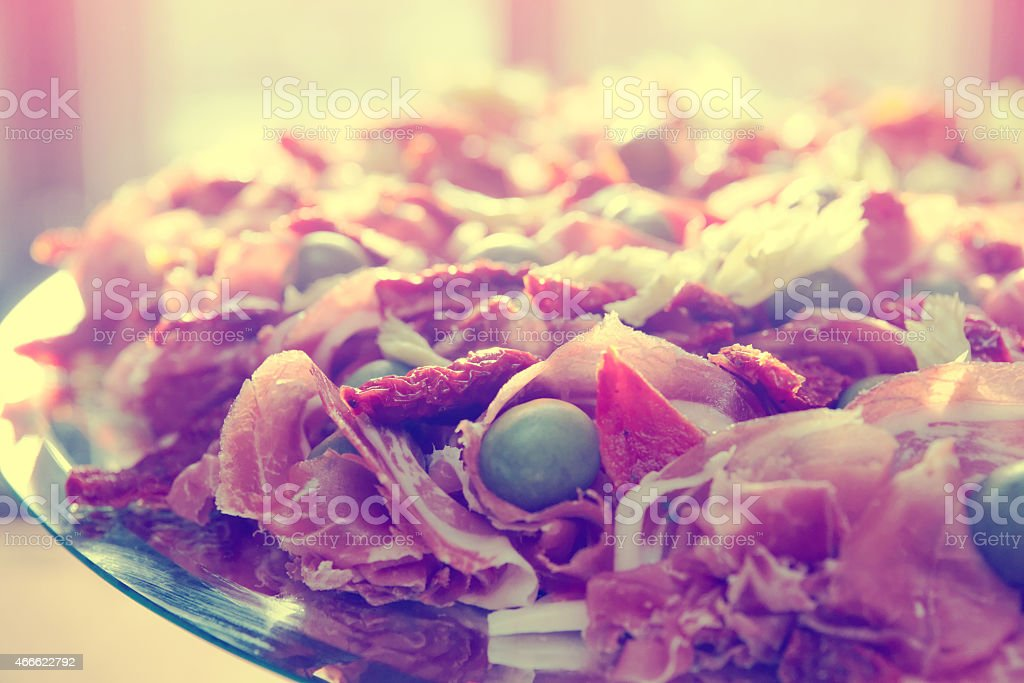 Platter with cured ham on table, toned stock photo