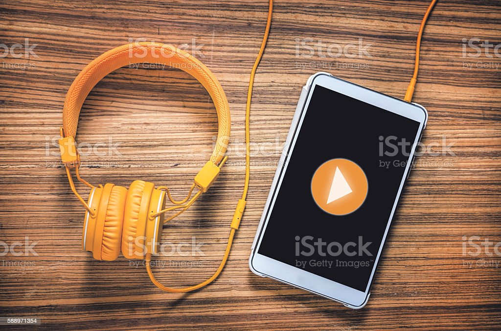 Play button on tablet with headphones on wooden table stock photo