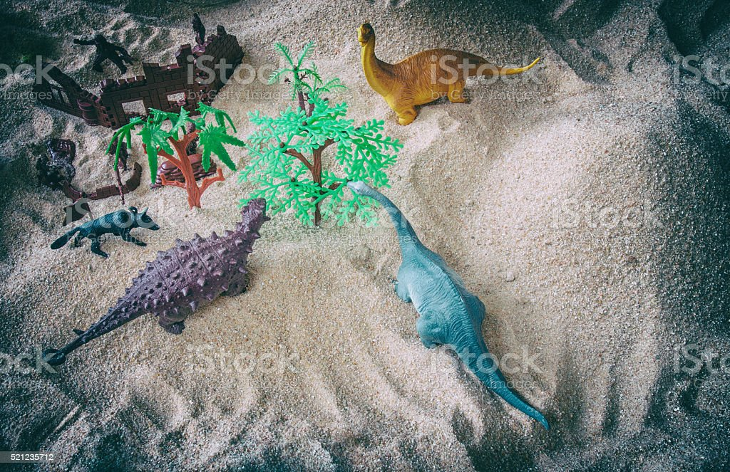 Play toys in sand with army fighting with dinosaur apatosaurus stock photo