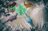 Play toys in sand with army fighting with dinosaur apatosaurus