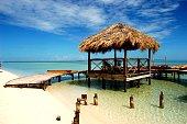 Playa de agua cristalina con muelle en construccion y bohío