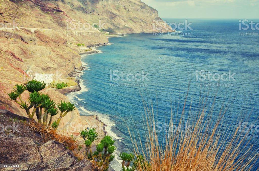 Playa de Las Gaviotas aerial view. Tenerife minimalist seascape with rocks. Filtered image, cross processed effect. stock photo