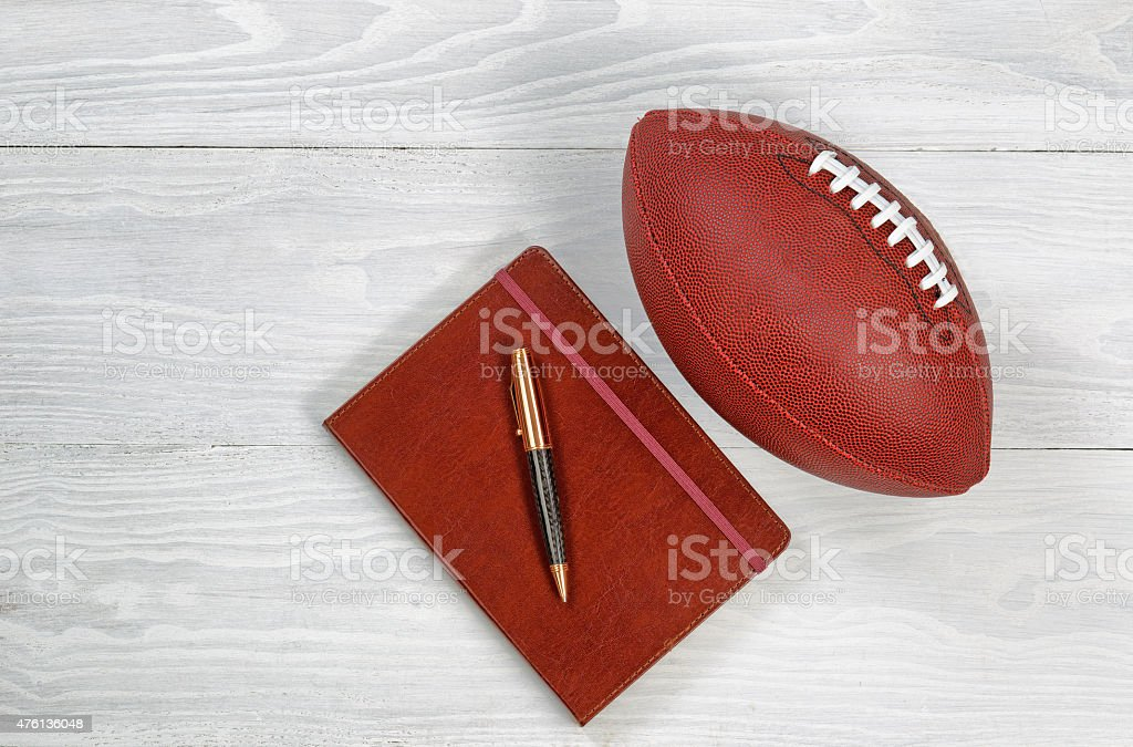 Playbook with Football on rustic white wood stock photo