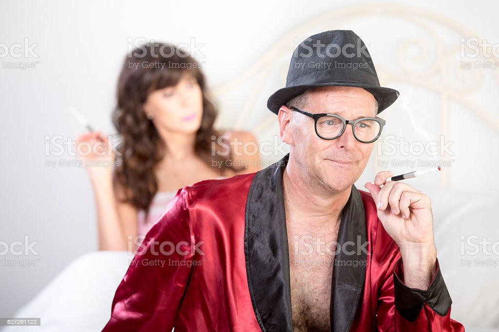Playboy and Woman in Bed Smoking stock photo