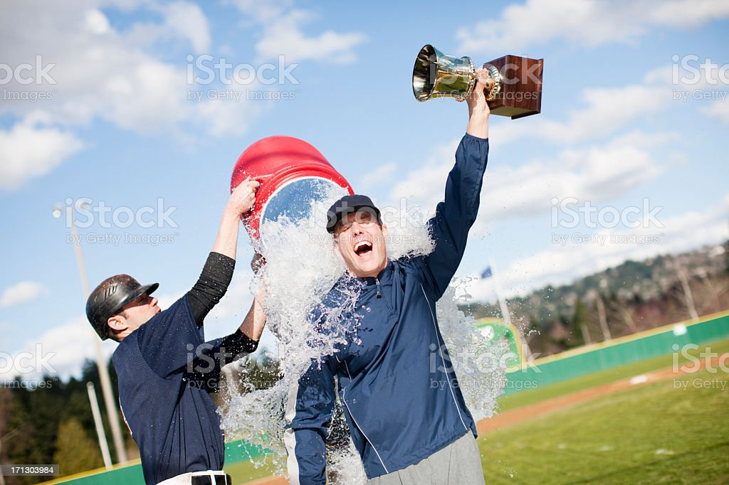 Player dumping Gatorade on coach holding a trophy stock photo
