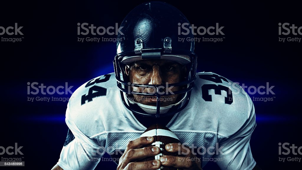 player gripping football stock photo