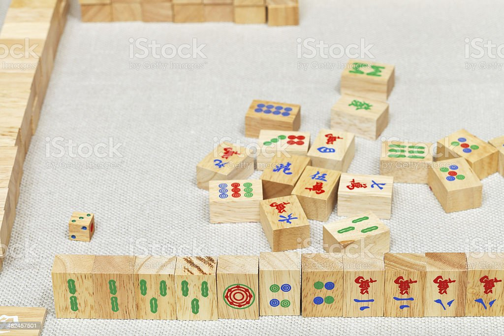 player hand from wooden tiles in mahjong game stock photo