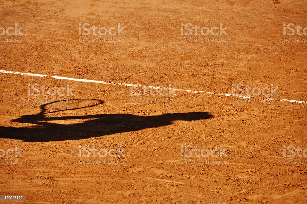 Player shadow on a clay tennis court royalty-free stock photo