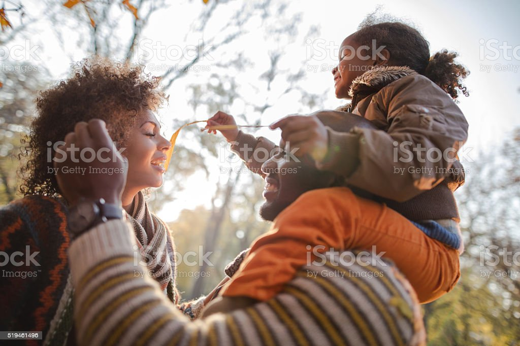 Playful African American family enjoying in nature during autumn. stock photo