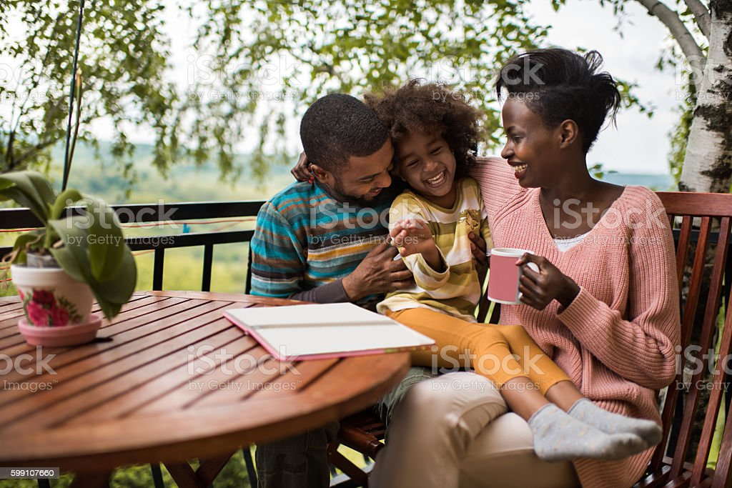 Playful African American family having fun on a terrace. stock photo