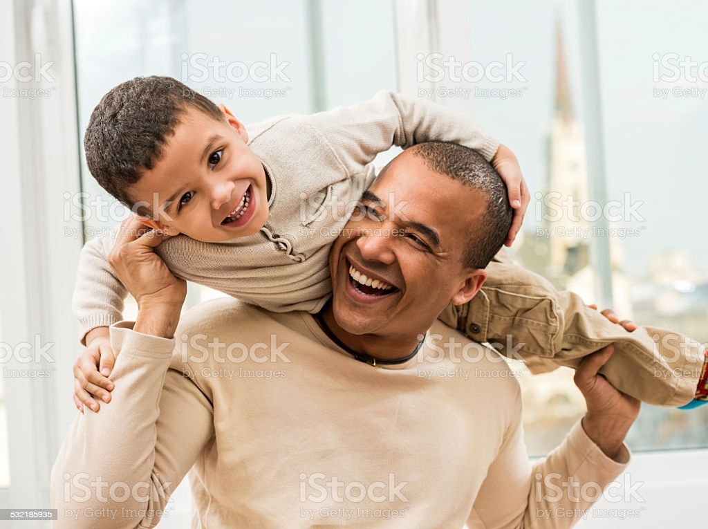 Playful African American father and son. stock photo