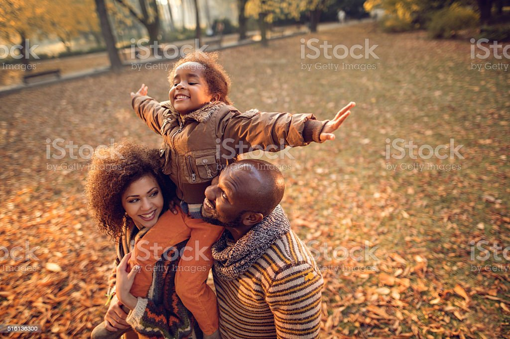 Playful African American little girl having fun with parents outdoors. stock photo