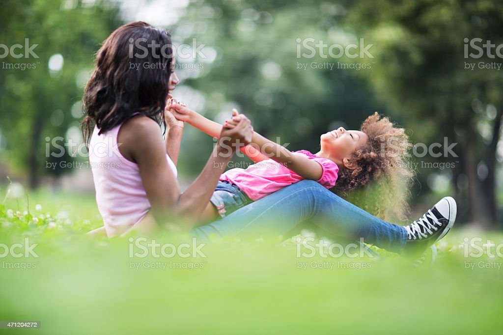 Playful African American mother and daughter having fun in grass. stock photo