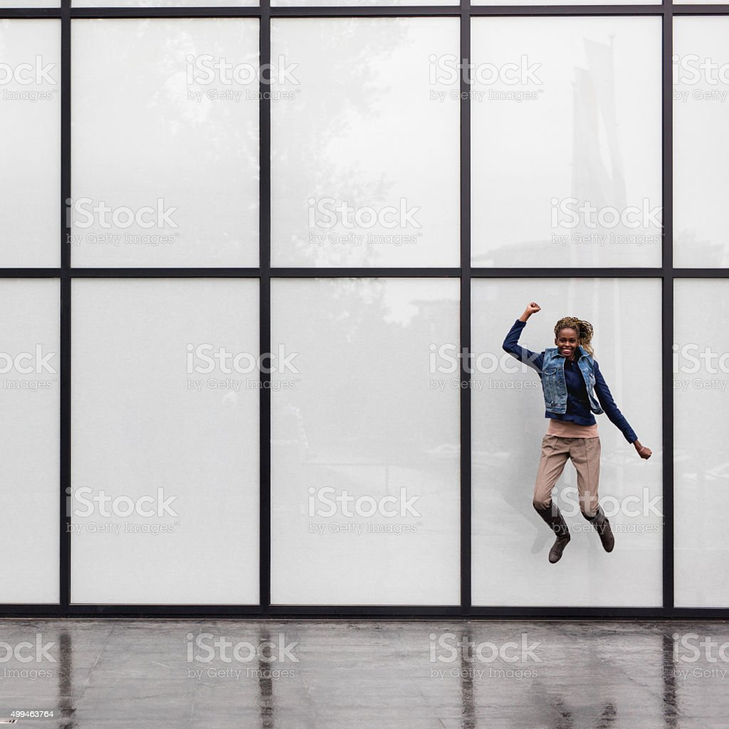 Playful African American woman jumping against curtain wall. stock photo
