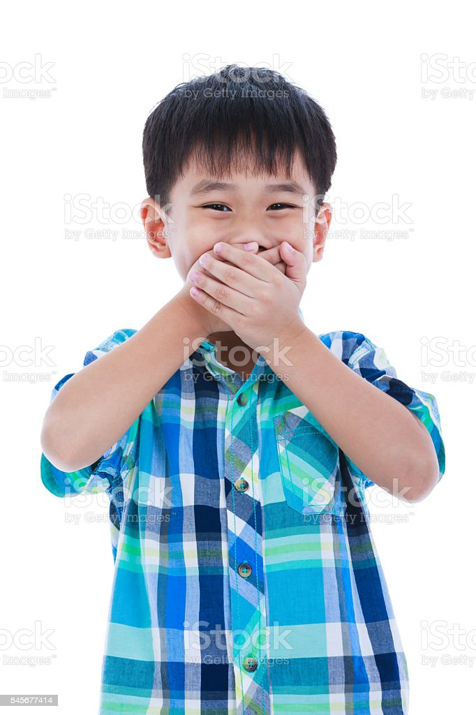 Playful asian boy covering his mouth. Isolated on white backgrou stock photo