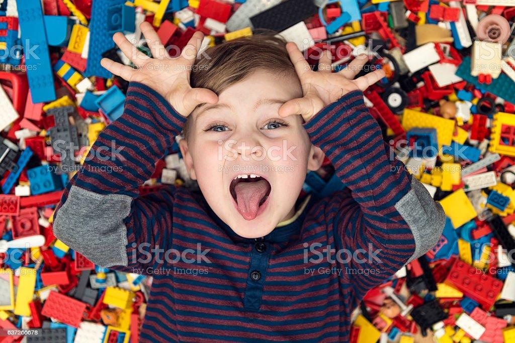 playful boy between plastic blocks stock photo
