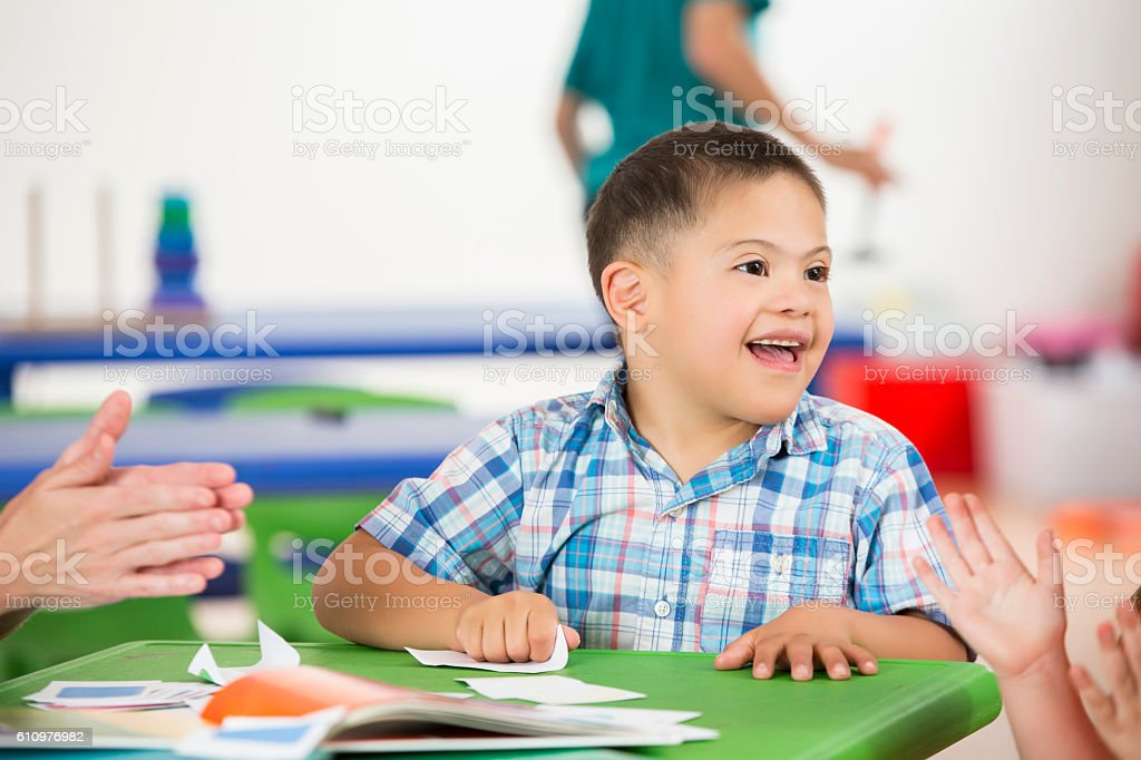 Playful boy with Down's Syndrom has fun with classmate stock photo