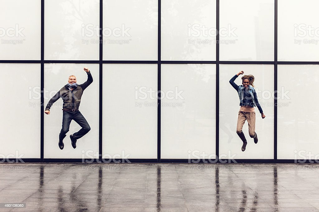 Playful business people jumping against rectangular curtain wall. stock photo